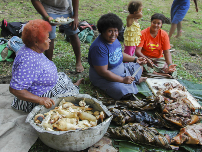 Fijian women serving the roasted pig baked in the earth oven (lovo)