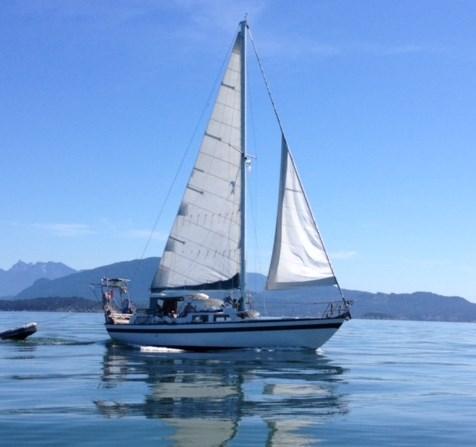 Alia motor-sailing on a glassy Salish Sea, headed for 'Isla des Acorn-Hornos'.