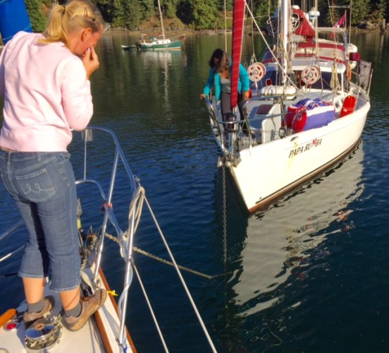 Heather on Blue Rose and Amanda on Papa Rumba patiently untangling the anchor rodes.
