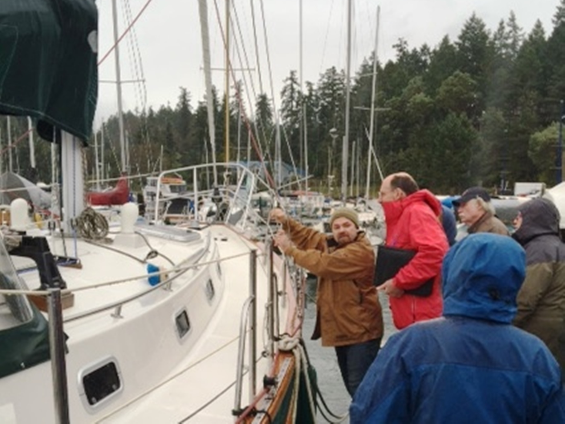 In blustery rain, Fleet members learned how to inspect standing rigging.